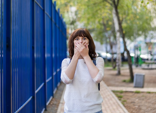 A beautiful brunette girl covered her mouth with her hands. surprised by the gesture. a girl in a white jacket is standing on the street.