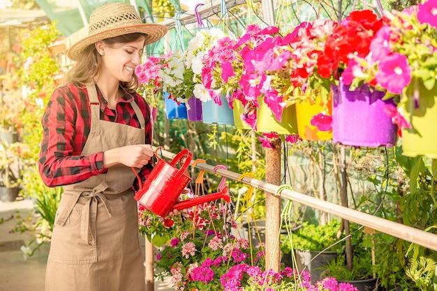 美しいブルネットの少女は、植物の苗床で花に水をまくことによってガーデニングを行います