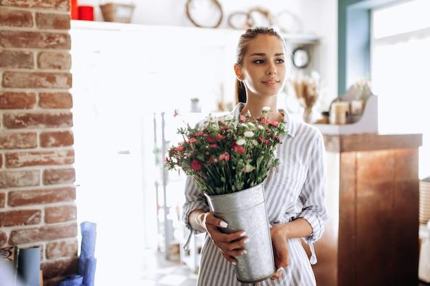 줄무늬 드레스를 입은 아름다운 브루네트 소녀는 꽃집에 분홍색과 흰색 국화가 든 꽃병을 들고 있습니다.