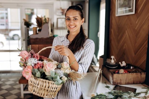 줄무늬 드레스를 입은 아름다운 브루네트 소녀는 꽃가게에 있는 바구니에 파스텔 색상의 신선한 꽃에서 꽃다발을 들고 있습니다.