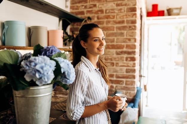 줄무늬 드레스를 입은 아름다운 갈색 머리 소녀가 밝은 파란색 호텐시아가 있는 꽃병 근처의 꽃집에 서서 컵을 들고 있습니다.