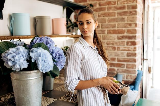줄무늬 드레스를 입은 아름다운 갈색 머리 소녀는 밝은 파란색 호르텐시아가 있는 꽃병 근처의 꽃집에 서 있습니다.