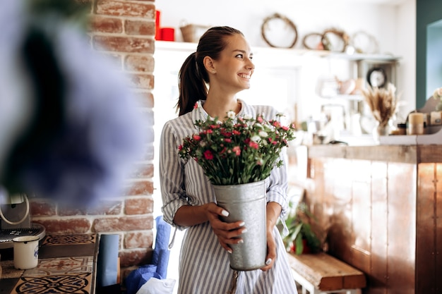 Beautiful brunette girl dressed in a striped dress holds a vase with pink and white chrysanthemums in the flower shop .