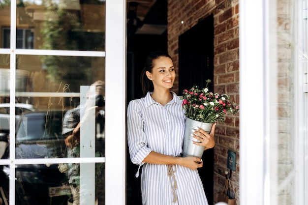 Beautiful brunette girl dressed in a striped dress holds a vase with pink and white chrysanthemums outside near the door .