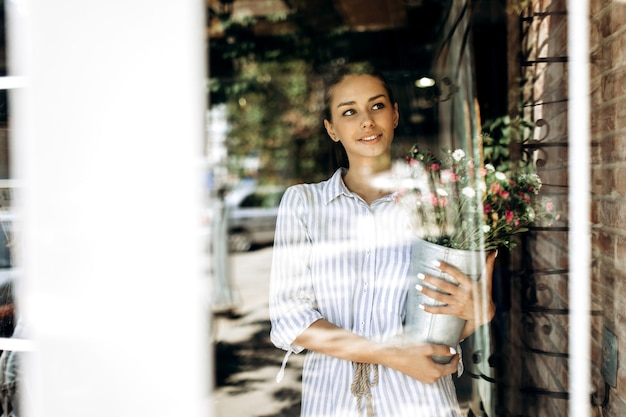 Beautiful brunette girl dressed in a striped dress holds a vase with pink and white chrysanthemums in sunlight .