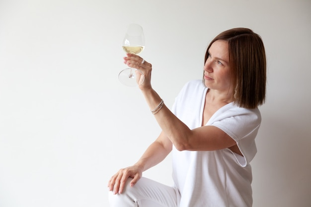 Beautiful brunette girl expert on white background looking on glass of white wine, holding by stem, assesses color, quality at professional degustation