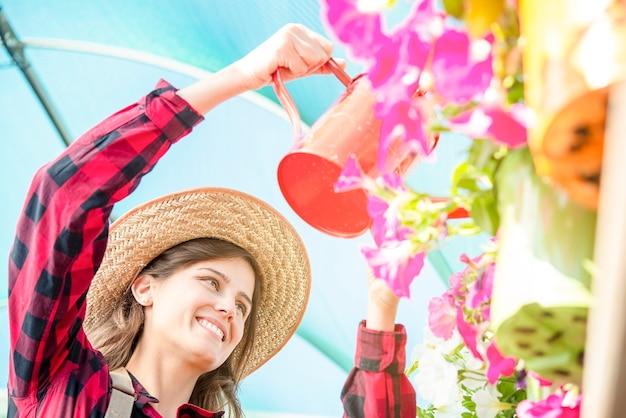 温室で花に水をまくガーデニングの美しいブルネットの少女