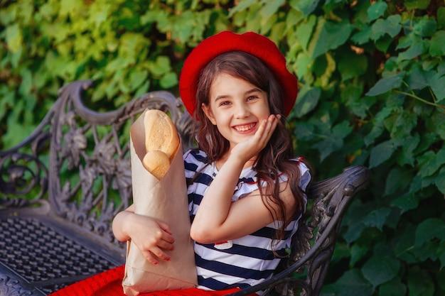 프랑스 바게트를 들고 아름 다운 갈색 머리 소녀