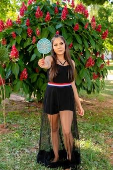 森の中でカラフルなロリポップを保持している美しいブルネットの少女。セレクティブフォーカス。
