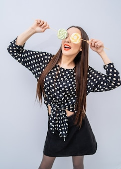 Beautiful brunette girl holds two lollipops near eyes. cheerful lady in dotted shirt over white background.