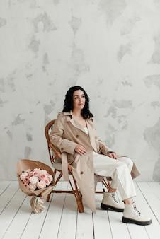 베이지 색 긴 트렌치 코트와 큰 부츠에 아름 다운 갈색 머리 소녀는 안락의 자에 앉아