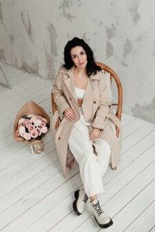 베이지 색 긴 트렌치 코트 흰색 바지와 큰 부츠에 아름 다운 갈색 머리 소녀는 꽃의 꽃다발과 함께 안락의 자에 앉아