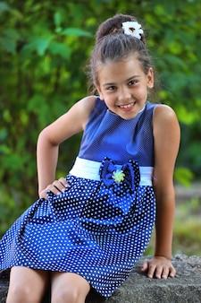 公園で夏に青い水玉模様のドレスを着た美しいブルネットの少女。自然の中でスタイリッシュな子供。高品質の写真