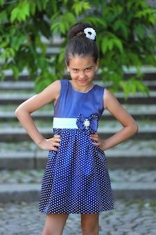公園の階段の階段に青い水玉模様のドレスを着た美しいブルネットの少女。高品質の写真