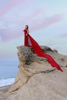 Красивая брюнетка девушка в красном платье с длинным шлейфом, стоящим в скалах