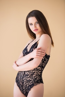 섹시 한 검은 끈 콤보 죄수 복 포즈 베이지 색 배경에 고립에서 아름 다운 갈색 머리 소녀. 패션 란제리. 럭셔리 여자.