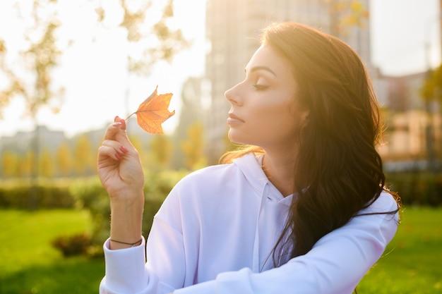 白いパーカーの美しいブルネットの少女は緑の都市公園に座って、柔らかな太陽の光の中で1つの秋の葉を保持します
