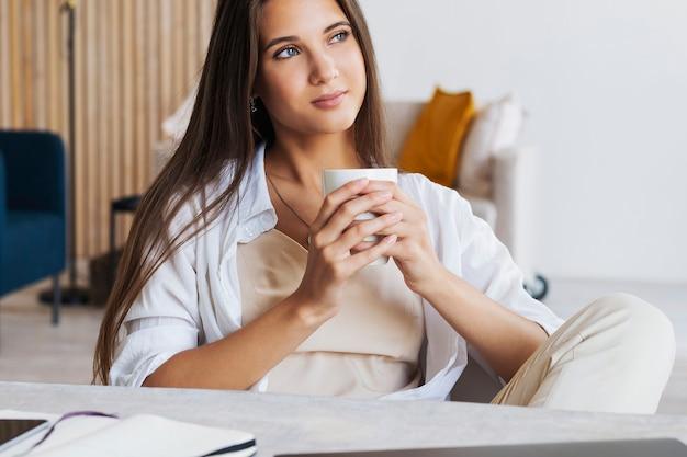 美しいブルネットの少女は、ラップトップの前のテーブルに座って、彼女の手で白いコーヒーを持っています。