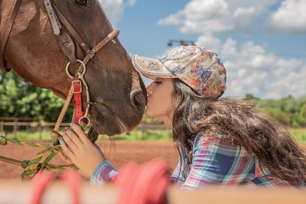 Beautiful brunette girl kissing her horse