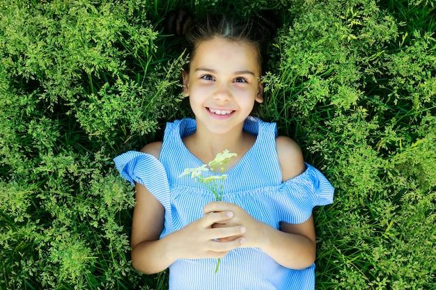 Красивая брюнетка девушка лежит на траве летом и улыбается. фото высокого качества