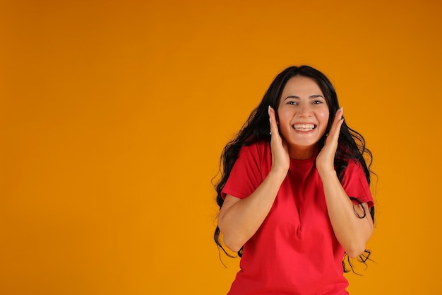 빨간 티셔츠를 입은 아름다운 갈색 머리 소녀는 노란색 배경에 놀란다