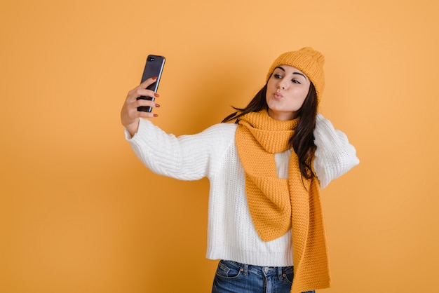 Beautiful brunette girl makes selfies in studio, she is in knitted hat and in scarf