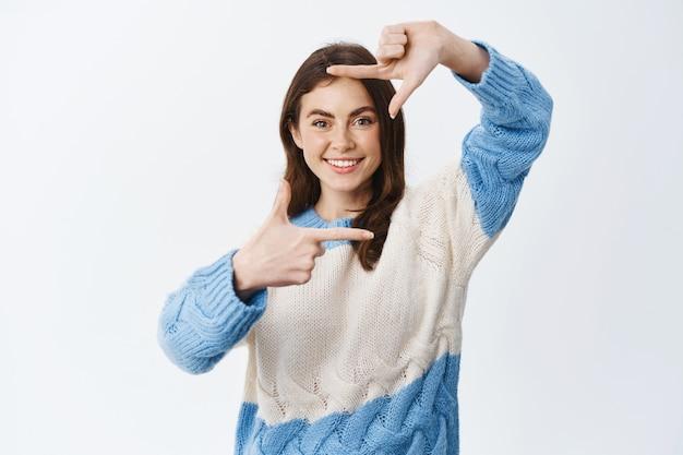 指でカメラフレームを作り、それを見て、瞬間をキャプチャするように幸せな笑顔、白い壁に立っている美しいブルネットの女の子