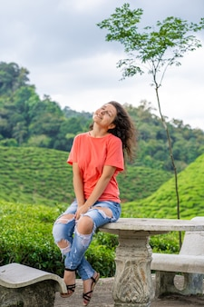 緑茶の茂みの間のお茶の谷の真ん中でポーズ美しいブルネットの少女。