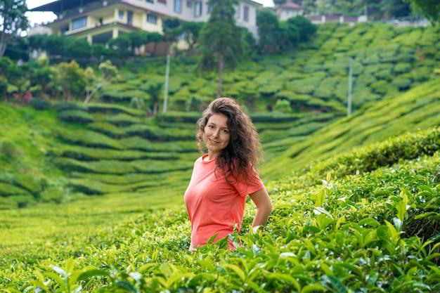 緑茶の茂みの間の茶の谷の真ん中でポーズ美しいブルネットの少女。