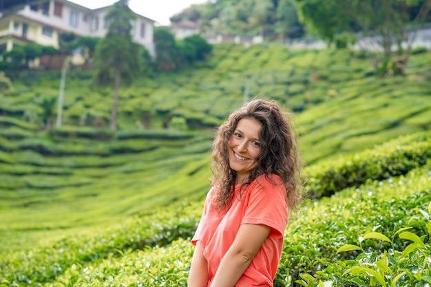 緑茶の茂みの間の茶の谷の真ん中でポーズをとる美しいブルネットの少女。