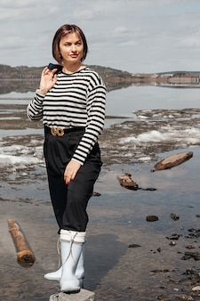 Beautiful brunette girl on the river bank. a girl in a striped vest and rubber boots holds a jacket in her hand. recreation and tourism.