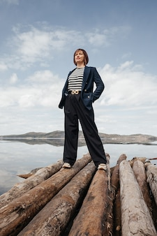 Beautiful brunette girl on the river bank. a girl in a striped vest and suit stands on logs on a sunny day. tourism and recreation.