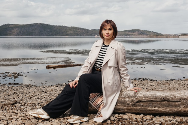 Beautiful brunette girl on the river bank. a girl in a striped vest, trousers and coat sits on a log. tourism and recreation.