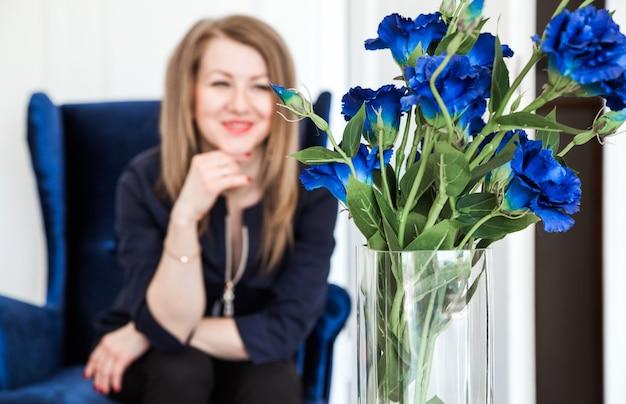 Красивая девушка брюнетка сидит в синем бархатном кресле и смотрит на букет синих цветов. женщина смотрит на букет и улыбается.