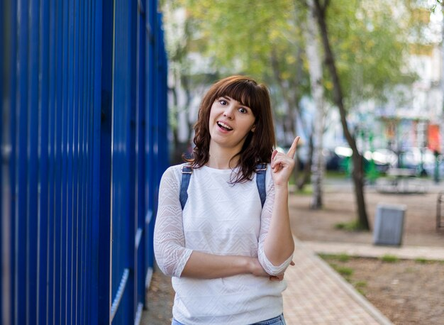 A beautiful brunette girl smiles and points her finger up. a girl in a white jacket is standing on the street.