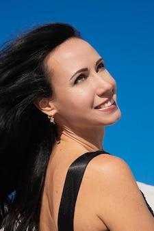 Красивая брюнетка девушка улыбается на фоне голубого неба. ветер развевает длинные волосы. слияние с природой и медитацией.
