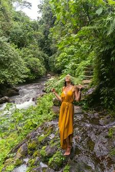 숲에서 강의 소리를 들으면서 돌 위에 서 있는 아름 다운 갈색 머리 소녀 프리미엄 사진