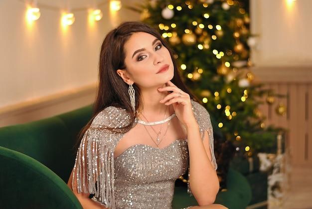 クリスマスツリーのガーランドライトと輝くイヤリングを身に着けている美しいブルネットの少女
