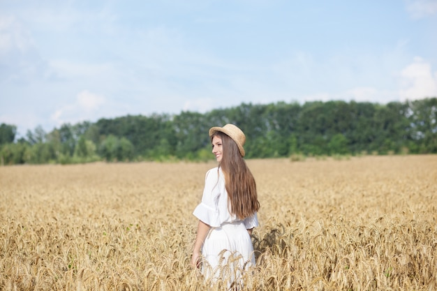 Beautiful brunette girl in white dress and  in straw hat standing in wheat field at sunset. harvesting