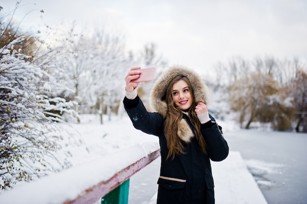 Beautiful brunette girl in winter warm clothing. model on winter jacket against frozen lake at park making selfie on phone.