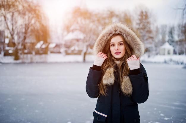 Beautiful brunette girl in winter warm clothing. model on winter jacket against frozen lake at park.