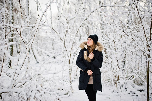 Beautiful brunette girl in winter warm clothing. model on winter jacket and black hat.