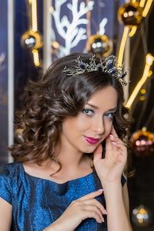 黄金の王冠、イヤリング、プロの夜メイクと美しいブルネットの少女。美容女性の顔。女王のイメージ。黒い髪、頭に冠、透明な肌、美しい顔、ふっくらした唇