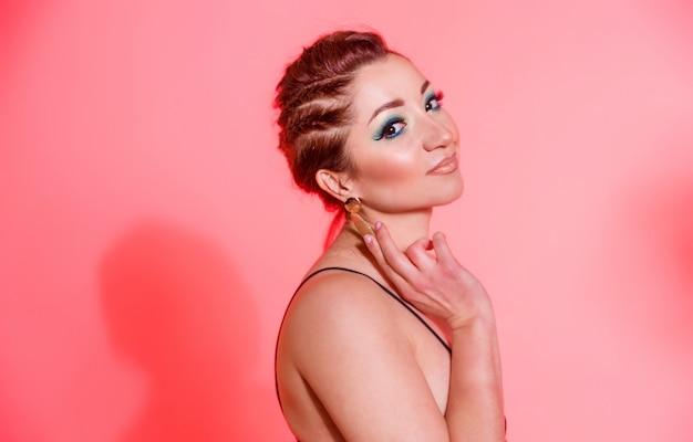 Красивая брюнетка с голубым макияжем, косичками и сексуальным черным топом позирует на красном фоне с леденцом в форме сердца. горизонтальное фото