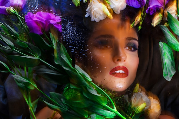 Beautiful brunette girl with bright make up lying among eustomas.