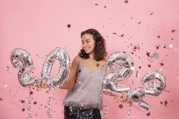 巻き毛とお祝いの服を着た美しいブルネットの少女は、紙吹雪とピンクの背景にポーズをとって、2022年の数字から銀の風船を持っています。