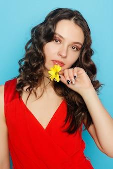 녹색 눈을 가진 아름다운 브루네트 소녀는 꽃, 피부 관리 개념, 뷰티 스파, 바이오 제품과 함께 파란색 배경에서 포즈를 취하는 신선한 피부를 만듭니다. 수평