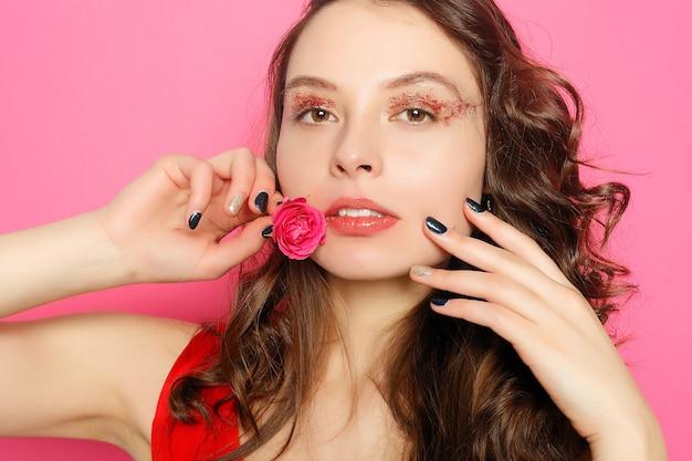 녹색 눈을 가진 아름다운 브루네트 소녀는 꽃, 피부 관리 개념, 미용 스파, 바이오 제품으로 분홍색 배경에서 포즈를 취하고 신선한 피부를 만듭니다. 수평