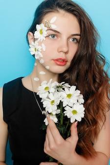 녹색 눈을 가진 아름다운 브루네트 소녀가 화장을 하고 꽃, 피부 관리 개념, 뷰티 스파, 바이오 제품으로 붉은 배경에서 포즈를 취하는 신선한 피부. 수평의