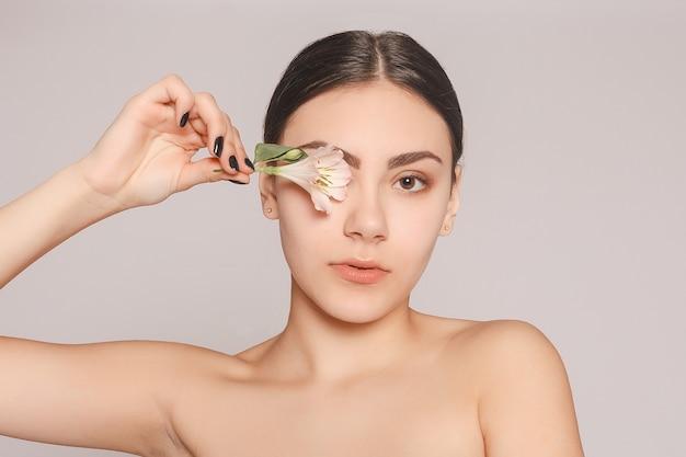 緑の目を持つ美しいブルネットの少女は、花、スキンケアのコンセプト、美容スパ、バイオ製品と赤い背景でポーズをとって新鮮な肌を構成します。水平